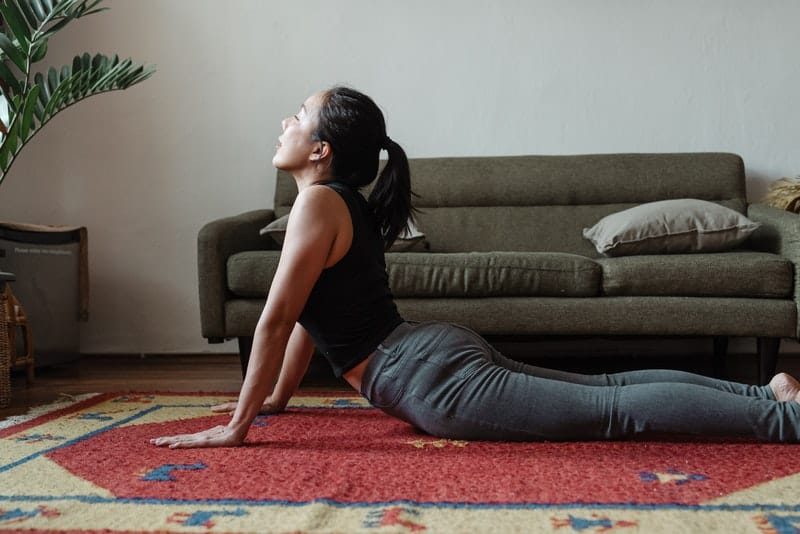 Auf dem Boden im Raum führt eine Frau eine Yoga-Übung durch