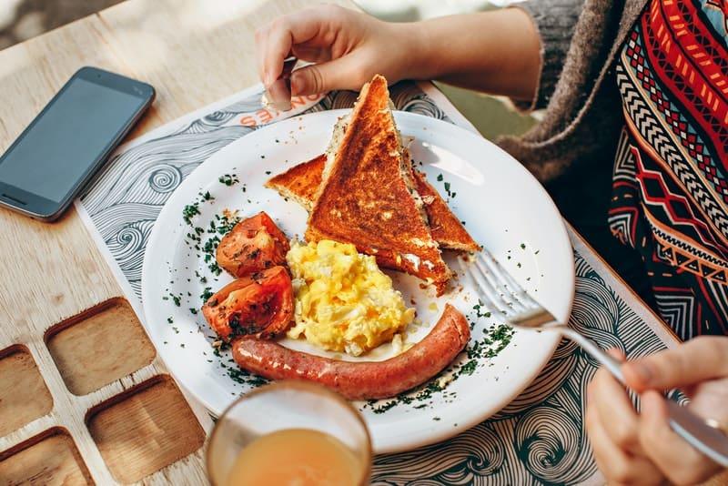 Auf dem Tisch steht ein Frühstück mit Eiern und Wurst