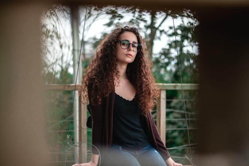 Auf dem Zaun sitzt ein trauriges Mädchen mit Brille