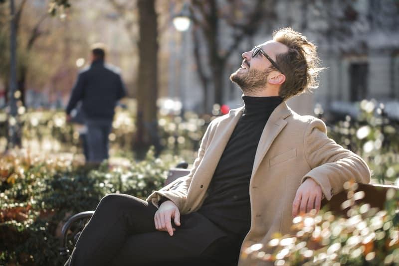 Auf einer Parkbank sitzt ein lächelnder Mann mit Brille und schaut zum Himmel hoch