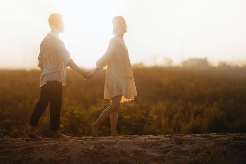 Barfuß Frauen und Männer gehen bei Sonnenuntergang auf dem Sand