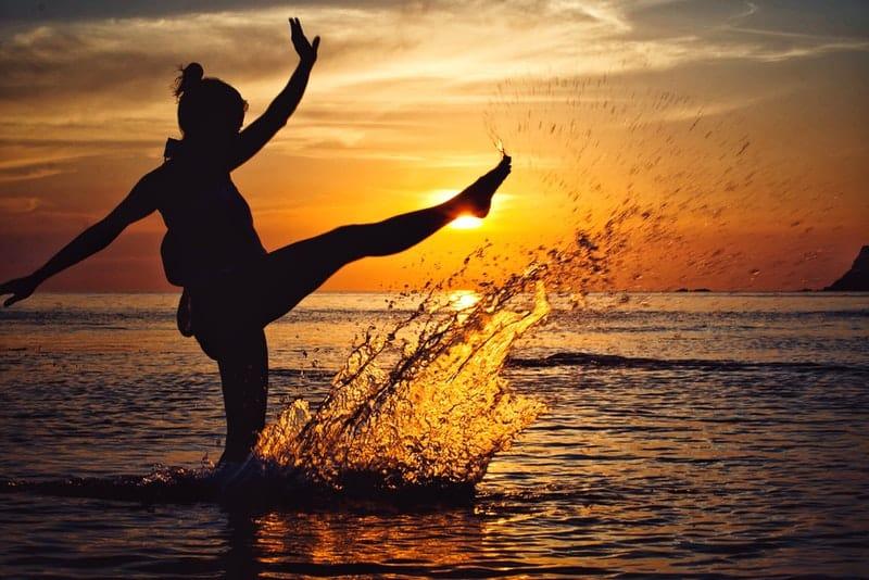Bei Sonnenuntergang steht eine Frau im Flachwasser des Meeres
