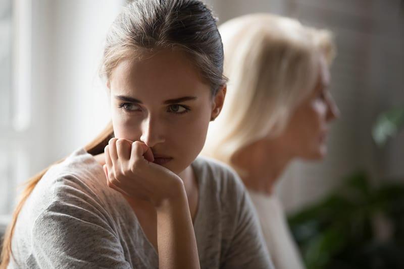 Beleidigte erwachsene Tochter und ältere Mutter sitzen Rücken an Rücken und vermeiden es, nach dem Kampf zu reden