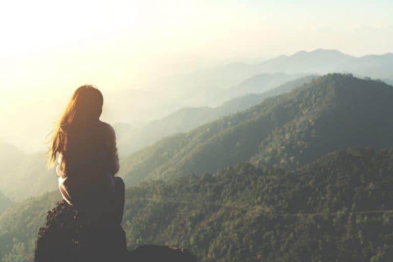 Das Mädchen sitzt auf einem Felsen oben auf dem Berg