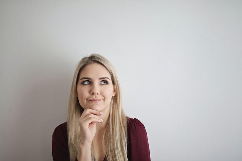 eine Frau mit blonden Haaren denkt und berührt das Kinn mit einer Hand