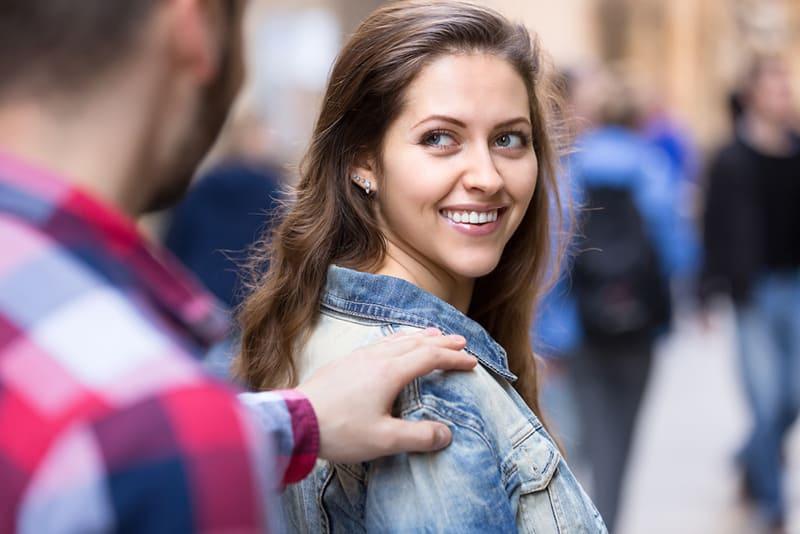 Der junge Mann hält eine schöne glückliche Frau auf einer Straße an, während sie ihre Schulter berührt
