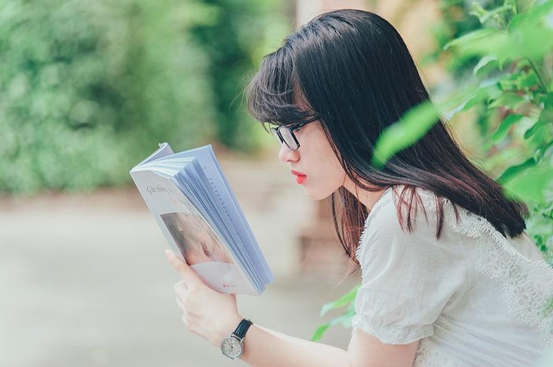 eine Frau, die ein Buch liest, während sie in der Nähe der Pflanzen sitzt