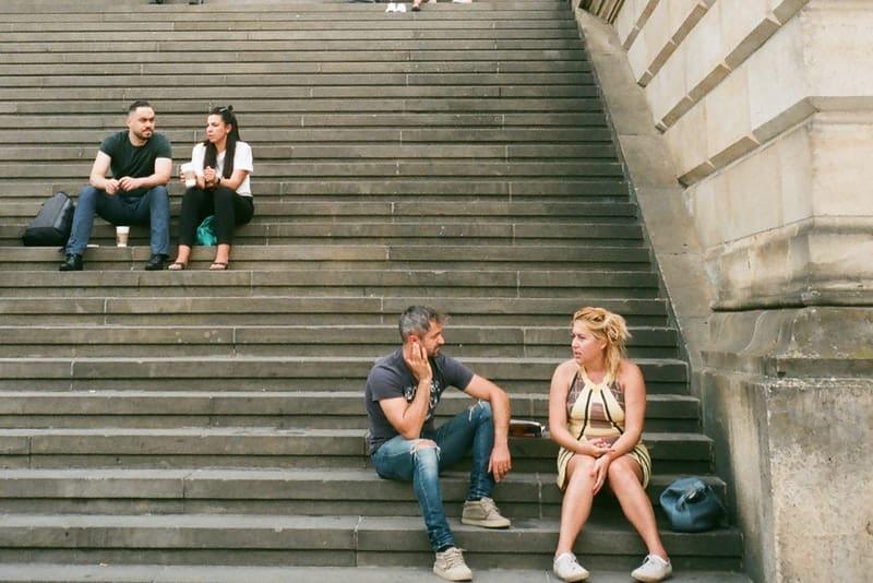 Draußen auf der Treppe sitzen zwei Paare und unterhalten sich