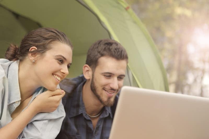 Draußen benutzen ein Mann und eine Frau mit einem Lächeln einen Laptop