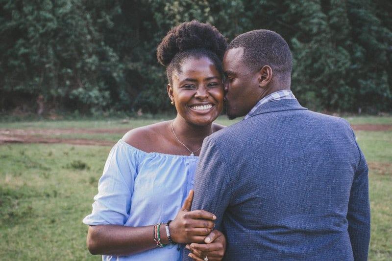 Draußen im Park küsst ein Schwarzer seine Frau auf die Wange