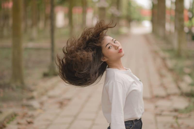 Draußen steht eine Chinesin in einem weißen Hemd mit schönen langen Haaren
