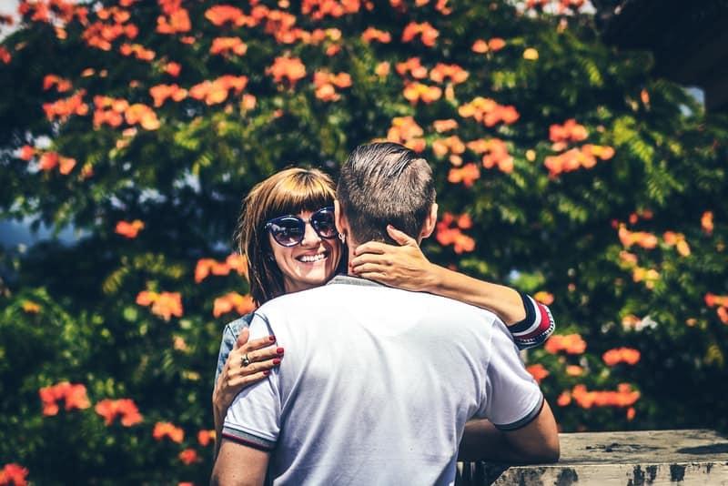 Draußen steht eine lächelnde Frau mit einer Sonnenbrille in den Armen eines Mannes