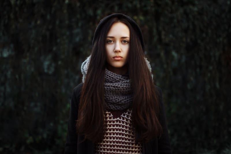 Draußen steht mit einem Schal um den Hals eine traurige Brünette mit schönen langen Haaren
