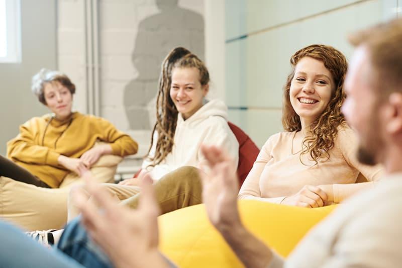 Drei Frauen hören einem männlichen Freund zu, während sie auf der Lazy-Tasche sitzen