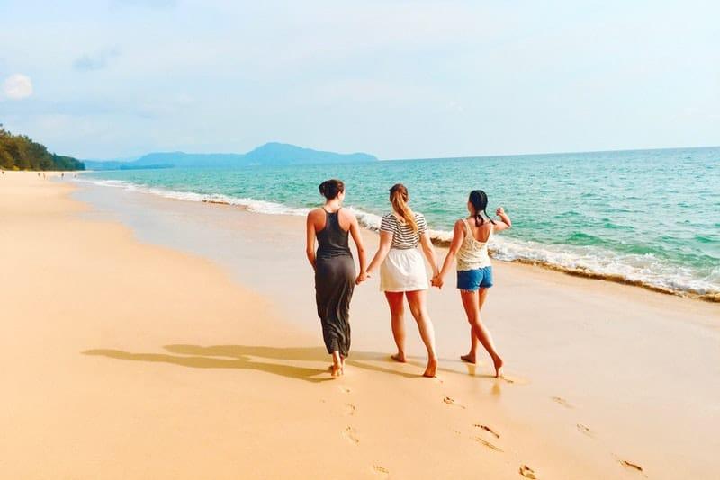 Drei Freunde gehen Händchen haltend am Strand entlang