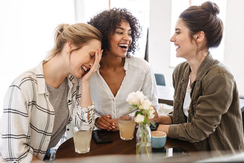 Drei Freunde lächeln und trinken Kaffee