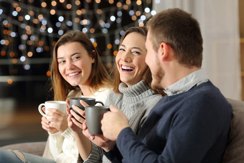 Drei Freunde reden und lachen, während sie auf der Couch sitzen und Tee trinken