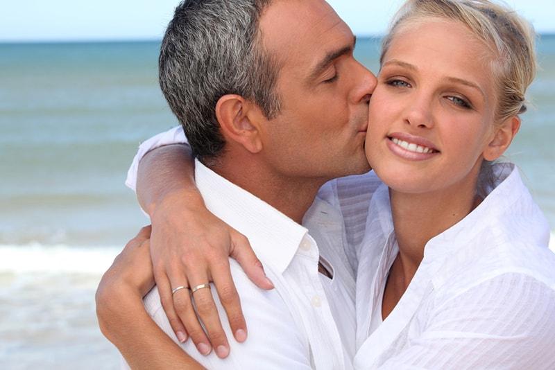 Ein älterer Mann küsste eine junge lächelnde Frau auf die Wange, während sie ihn umarmte
