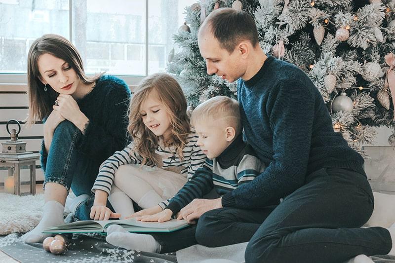 Ein Mädchen und ein Junge lesen ein Buch und sitzen zwischen einem Mann und einer Frau neben dem Weihnachtsbaum