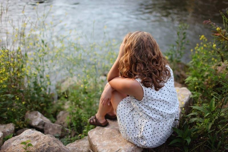 Ein Mädchen in einem weißen Tupfenkleid sitzt auf einem Felsen über dem Fluss