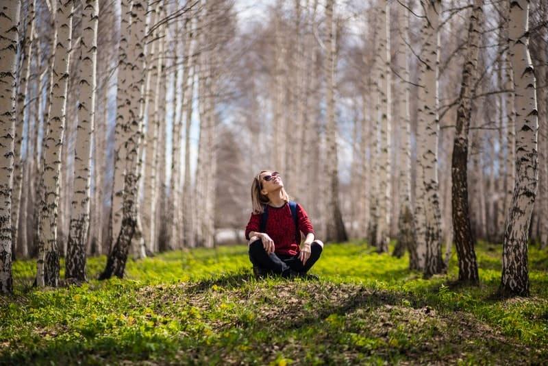 Ein Mädchen sitzt im Gras in einem Wald