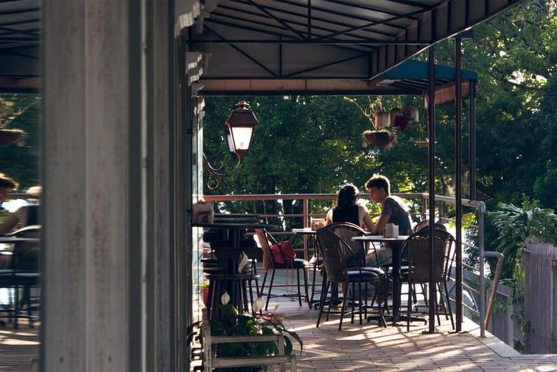 Ein Mädchen und ein junger Mann sitzen auf der Terrasse eines Cafés und unterhalten sich