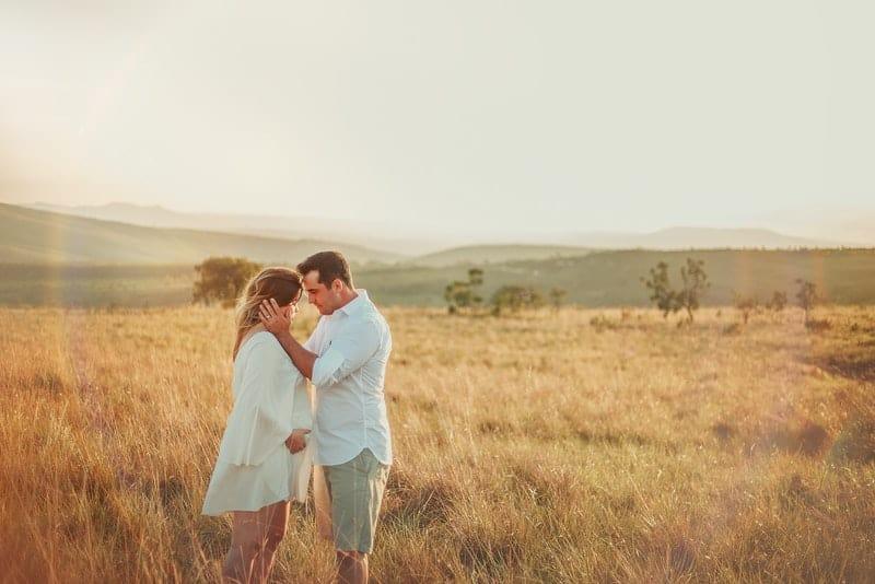 Ein Mann auf einem Feld hält romantisch eine Frau am Kopf