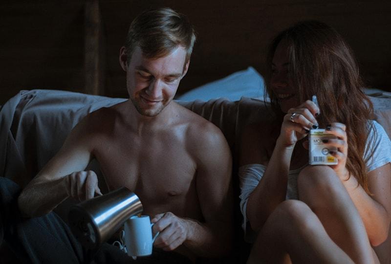 Ein Mann, der Kaffee in die Tasse füllt, sitzt neben einer Frau, die im dunklen Raum einen Saft hält