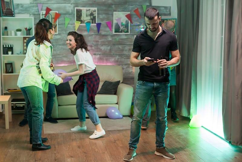 Ein Mann benutzt sein Smartphone auf einer Party, während seine Freunde tanzen
