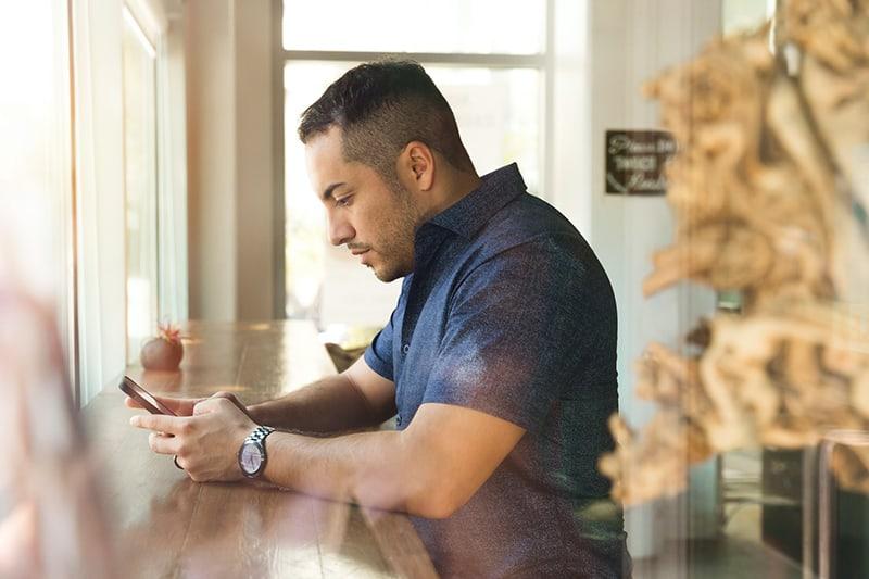 Ein Mann tippt eine Nachricht auf sein Smartphone, während er an der Theke steht