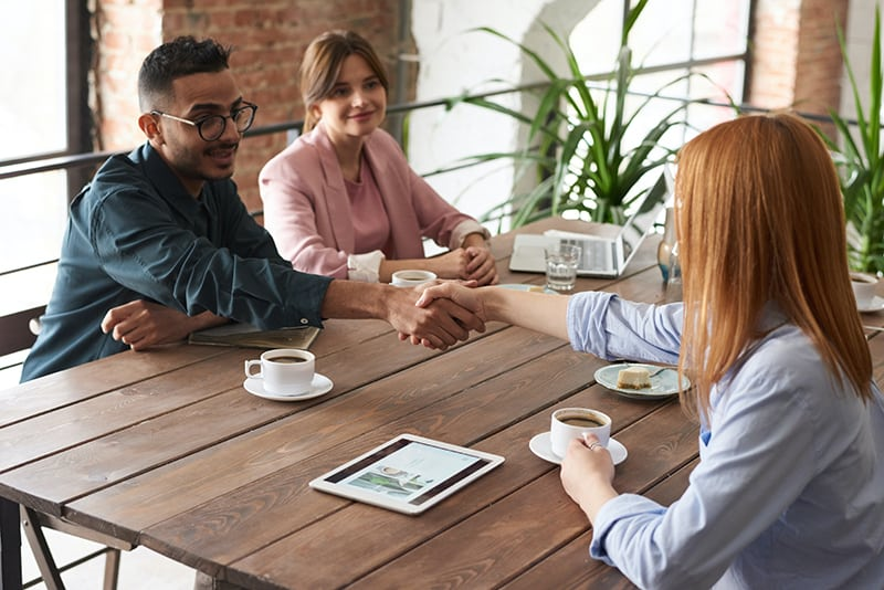 Ein Mann, der einer Frau die Hand schüttelt, während er mit einem gemeinsamen Freund am Tisch sitzt