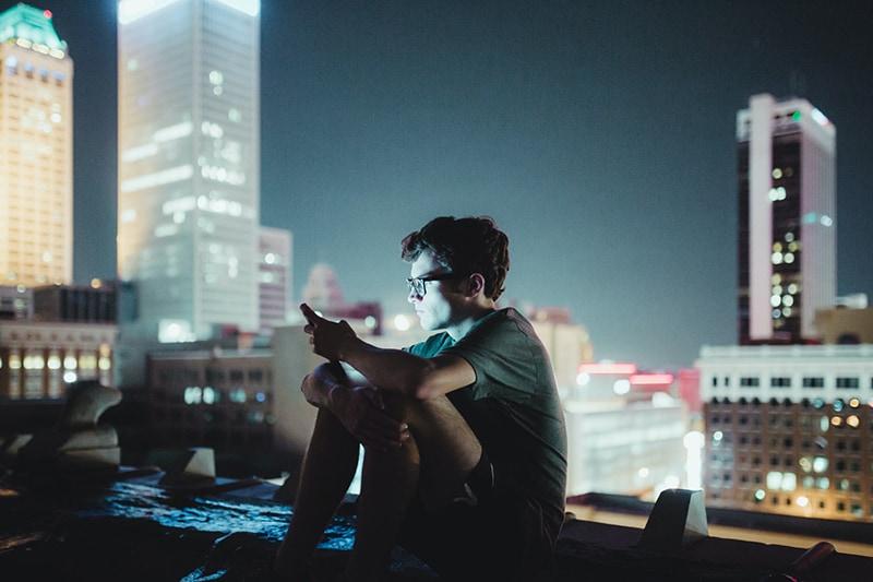 Ein Mann, der nachts oben auf dem Gebäude sitzt und ein Smartphone benutzt