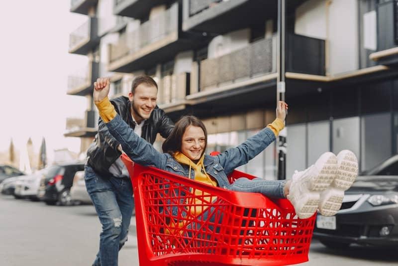 Ein Mann fährt ein Mädchen in einem Einkaufswagen