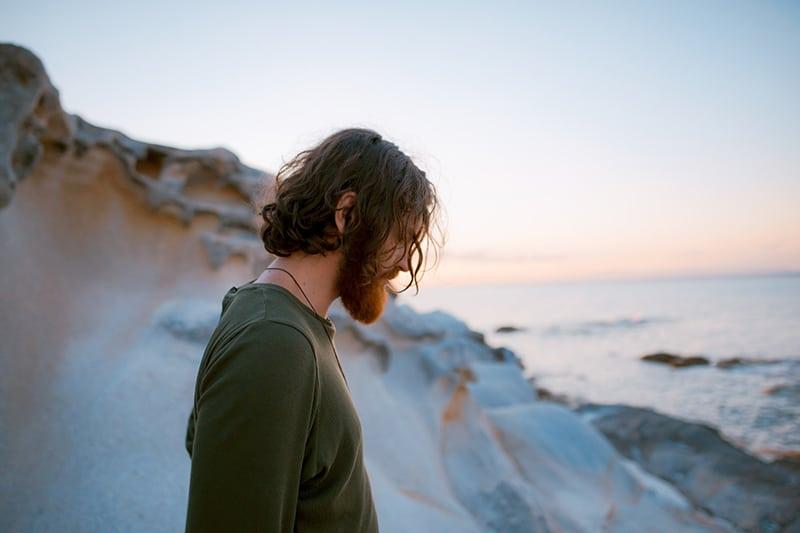 Ein Mann im grünen Hemd schaut nach unten, während er auf dem Felsen in der Nähe des Gewässers steht