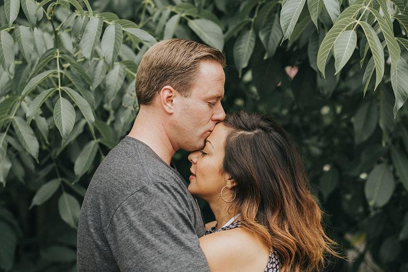 Ein Mann küsst eine Frau auf die Stirn, während er in der Nähe von grünen Pflanzen steht