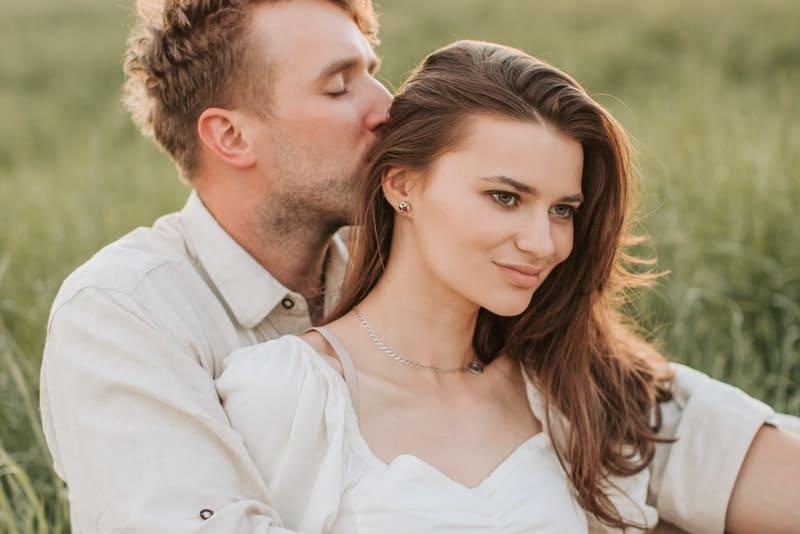 Ein Mann küsst die Haare einer zufriedenen Brünetten