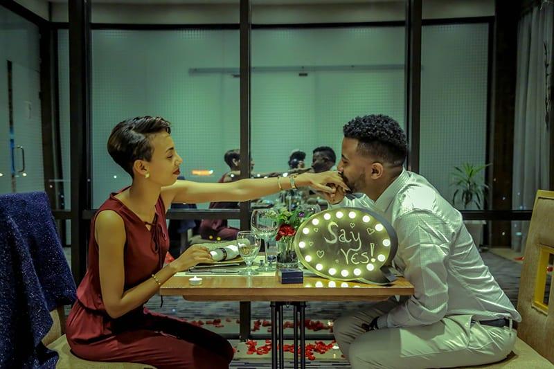 Ein Mann küsste die Hand seiner Verlobten während eines Vorschlags im Restaurant