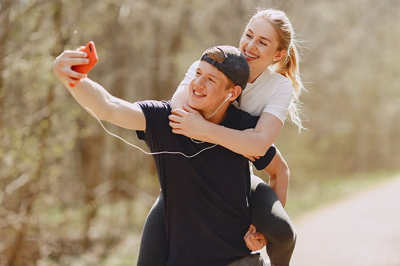 Ein Mann macht ein Selfie von ihm und seiner Freundin, während er sie auf seinem Rücken trägt
