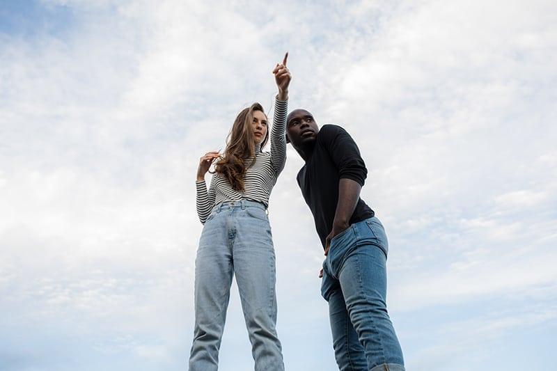Ein Mann mit den Händen in den Taschen stand in der Nähe des Mädchens und zeigte mit einem Finger irgendwo hin