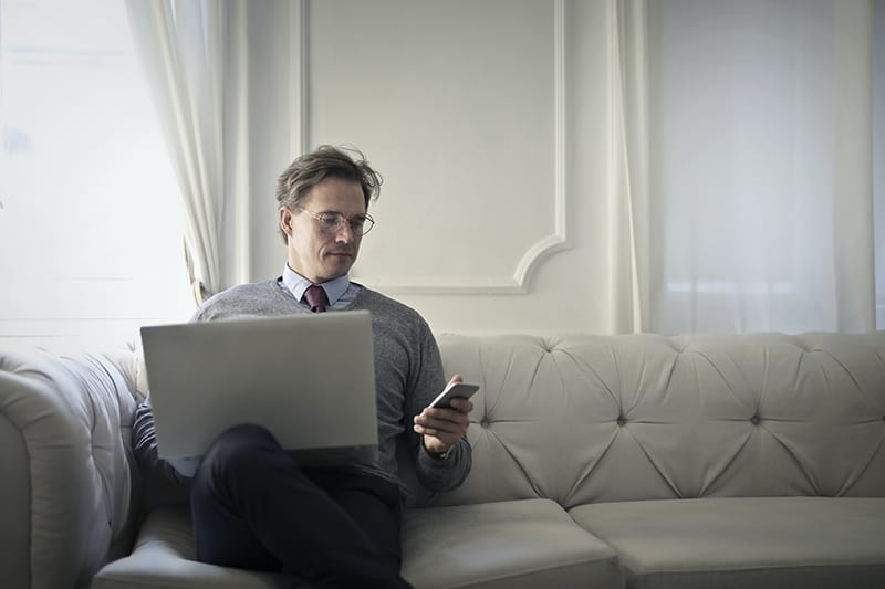 Ein Mann mit einem Smartphone sitzt auf dem Sofa und hat einen Laptop auf dem Schoß