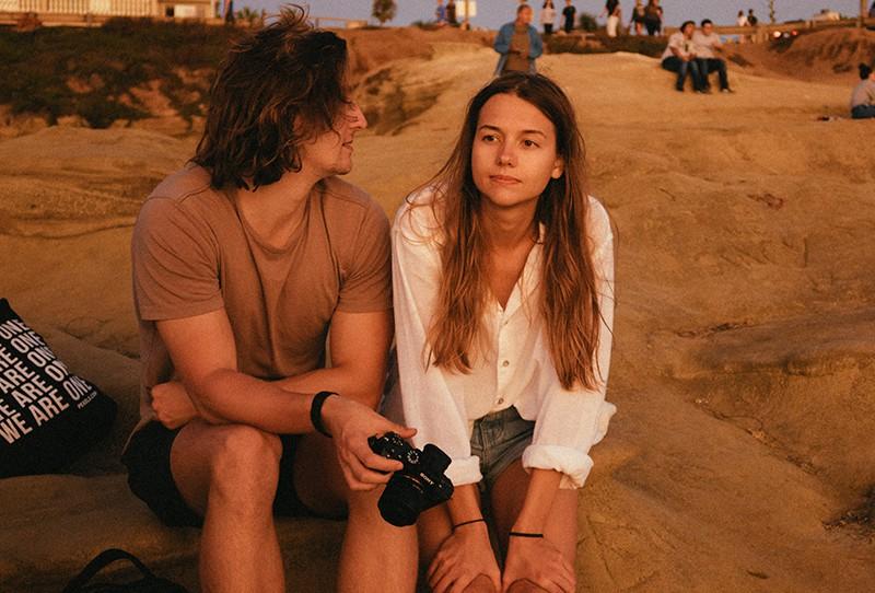 Ein Mann schaut zu einer Frau, die neben ihm auf den Felsen sitzt