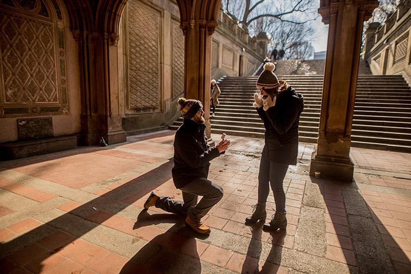Ein Mann schlägt seine Freundin vor, während er in der Nähe der Treppe kniet