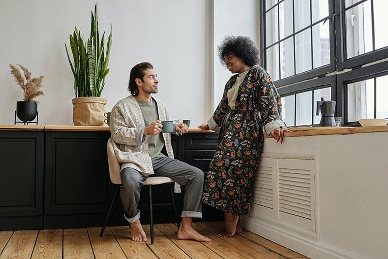Ein Mann sitzt auf dem Stuhl und hört seiner Freundin zu, die vor ihm steht