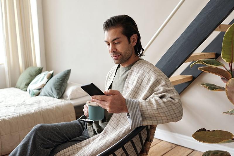 Ein Mann sitzt im Sessel im Schlafzimmer und schaut auf das Smartphone, während er Kaffee trinkt