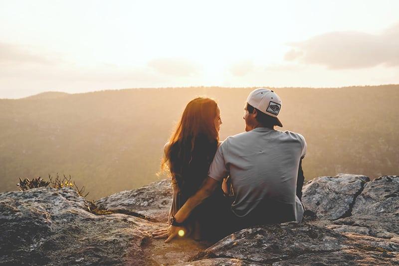Ein Mann sitzt in der Nähe einer Frau, während er während des Sonnenuntergangs auf dem Felsen sitzt