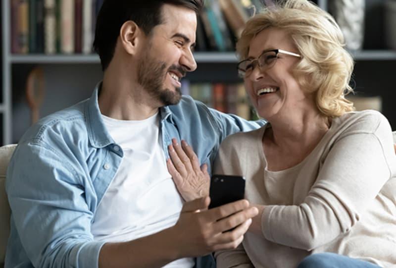 Ein Mann sitzt mit seiner Mutter auf der Couch und lacht, während er ein Selfie-Foto macht