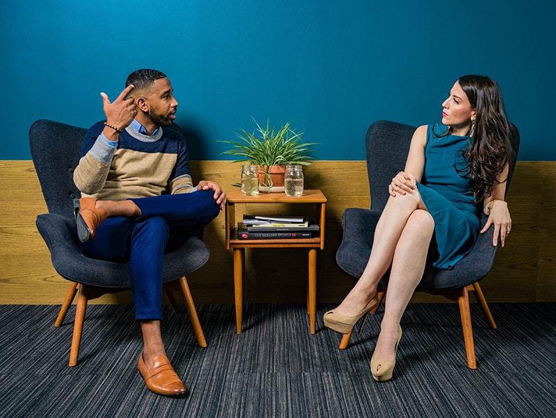 Ein Mann spricht mit einer Frau, während er zusammen am Tisch sitzt