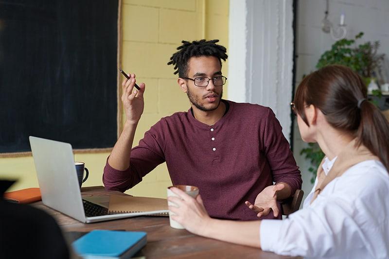 Ein Mann spricht mit seiner Freundin, während er am Schreibtisch sitzt