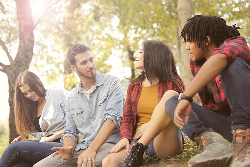 Ein Mann spricht und schaut zu einem lächelnden Mädchen, während er mit Freunden im Wald sitzt