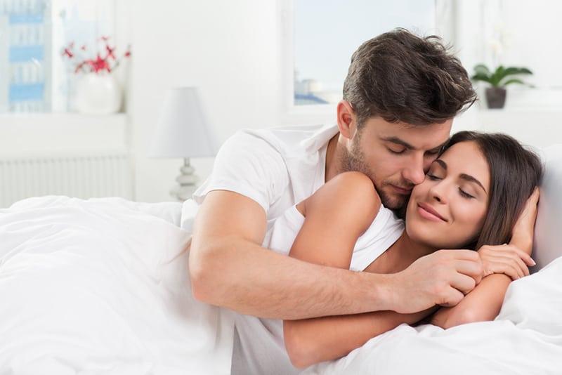 Ein Mann umarmt eine Frau von hinten, während er im Bett liegt